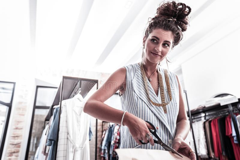 Πολυάσχολος δημιουργικός σχεδιαστής μόδας που κόβει τα νέα σκίτσα που κρατούν το ψαλίδι στο χέρι της στοκ εικόνα με δικαίωμα ελεύθερης χρήσης