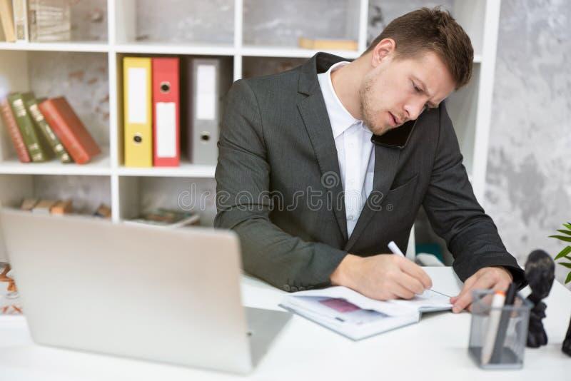 Πολυάσχολος διαχειριστής με φορητό υπολογιστή που κάθεται στο γραφείο του κρατώντας σημειώσεις στο planner και κάνοντας τηλεφωνικ στοκ φωτογραφίες με δικαίωμα ελεύθερης χρήσης