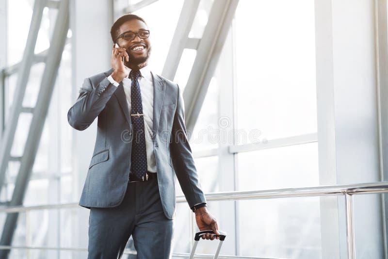 Πολυάσχολος επιχειρηματίας Afro που μιλά στο τηλέφωνο, που φθάνει στον αερολιμένα στοκ εικόνες