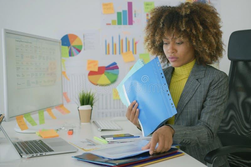 Πολυάσχολος εργαζόμενος που κοιτάζει αν και έγγραφα στοκ εικόνα με δικαίωμα ελεύθερης χρήσης