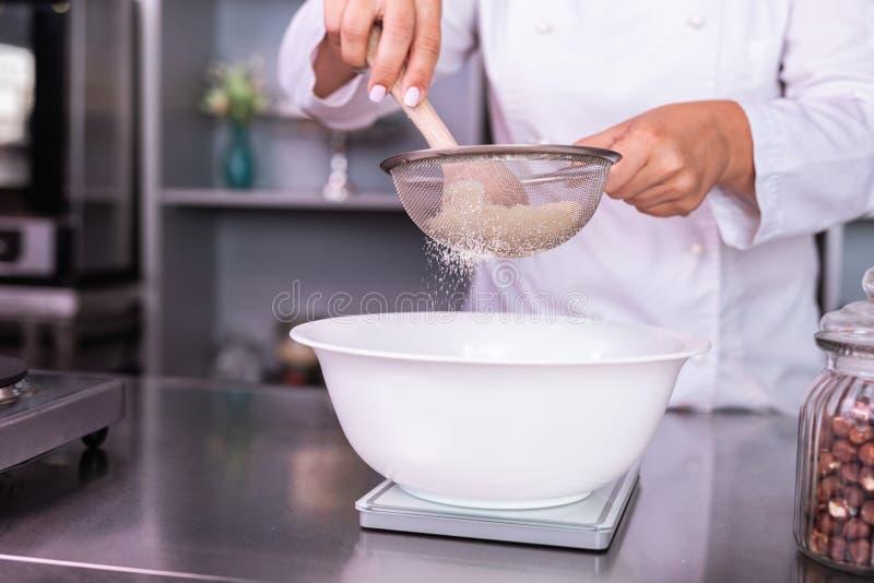 Πολυάσχολο αλεύρι αμπαρώματος ζαχαροπλαστών μαγειρεύοντας τη γλυκιά πίτα στοκ φωτογραφία με δικαίωμα ελεύθερης χρήσης