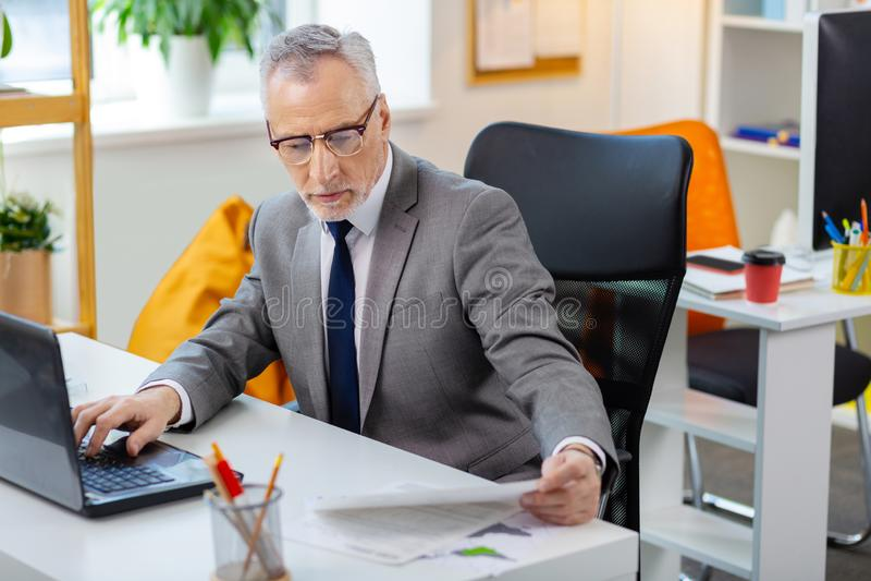Πολυάσχολο κουρασμένο γκρίζος-μαλλιαρό άτομο στα σαφή γυαλιά που διαβάζουν τα έγγραφα και που ελέγχουν το lap-top στοκ φωτογραφία