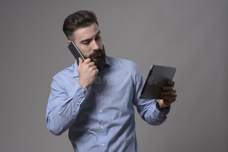 Πολυάσχολο νέο έξυπνο περιστασιακό γενειοφόρο άτομο που μιλά στο κινητό τηλέφωνο και που προσέχει στον υπολογιστή ταμπλετών στοκ εικόνα με δικαίωμα ελεύθερης χρήσης