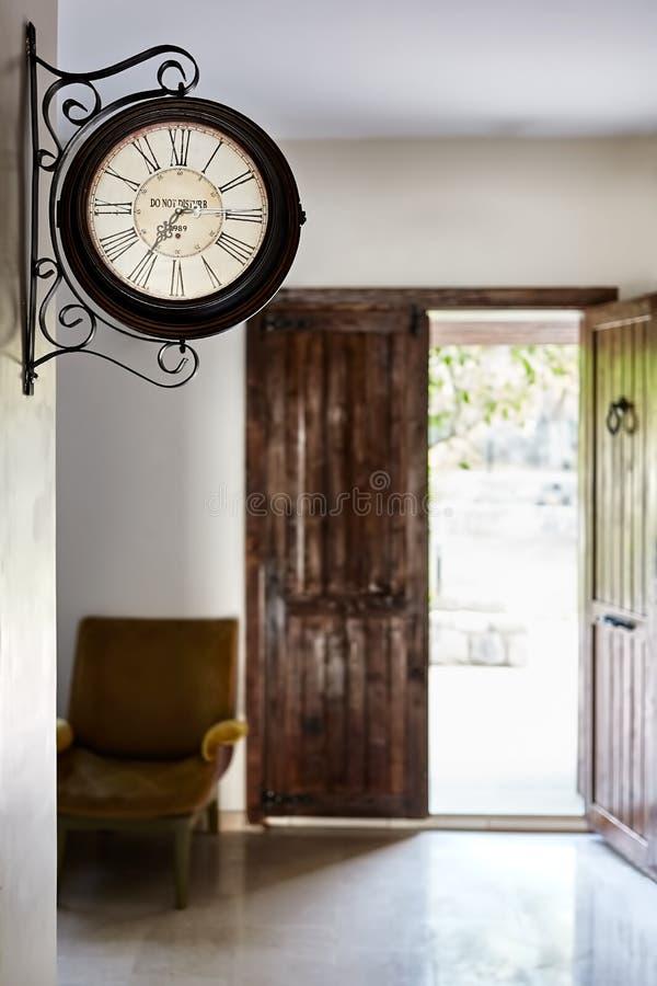 Πολυθρόνα ρολογιών τοίχων και και παλαιά αγροτική πόρτα στοκ φωτογραφία με δικαίωμα ελεύθερης χρήσης