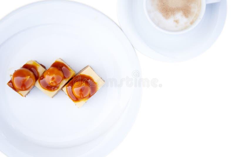 Πολυσέλιδα κέικ κρέμας σε λευκό πιάτο με ένα φλιτζάνι καφέ Ζαχαρώδη προϊόντα, διάλειμμα στην εργασία Απομονωμένες εικόνες στοκ εικόνες
