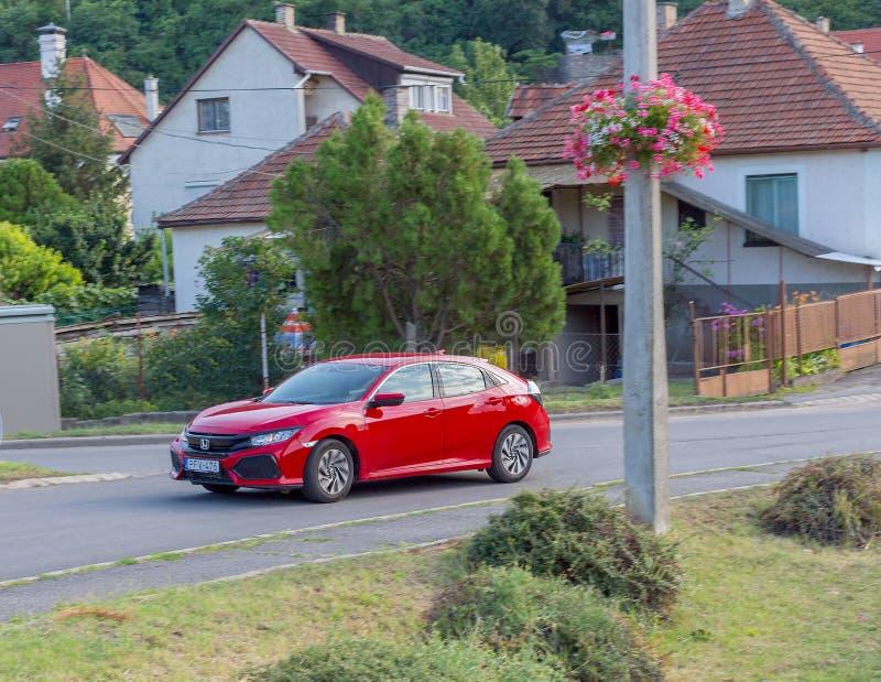 Πολυτελές κόκκινο αυτοκίνητο Honda Civic στο δρόμο μιας μικρής πόλης στοκ φωτογραφία