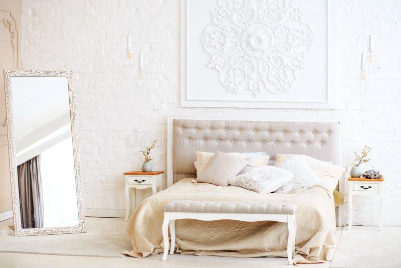 Πολυτελής κρεβατοκάμαρα με τους πίνακες κρεβατιών και πλευρών και έναν καθρέφτη Συμπυκνωμένος στοκ εικόνα
