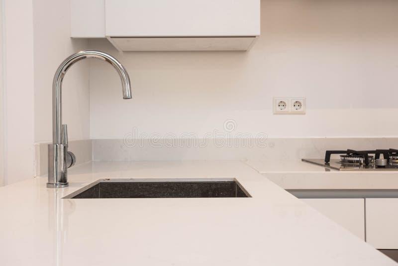 Πολυτελής σύγχρονη κουζίνα με το νεροχύτη, σύγχρονη μονάδα κουζινών με την επιχρωμιωμένη σύγχρονη άσπρη καθαρή έννοια κρουνών στοκ φωτογραφία