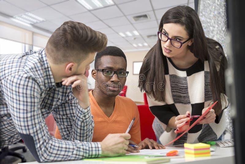 Πολυφυλετική σύγχρονη εργασία επιχειρηματιών που συνδέεται με τις τεχνολογικές συσκευές όπως την ταμπλέτα και το lap-top στοκ εικόνες