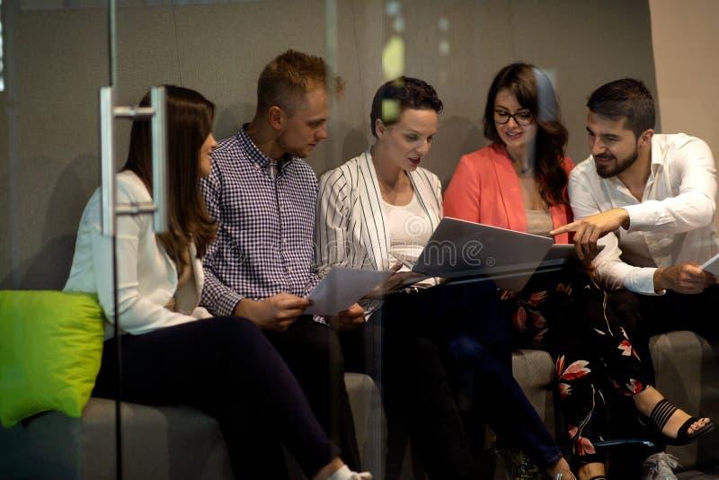 Πολυφυλετικοί δημιουργικοί νέοι στο σύγχρονο γραφείο Η ομάδα νέων επιχειρηματιών εργάζεται μαζί με το lap-top στοκ εικόνες