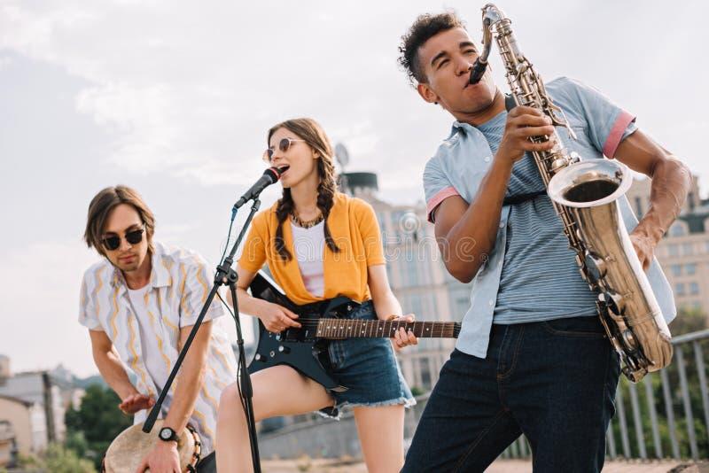 Πολυφυλετικοί νέοι με την κιθάρα djembe και την εκτέλεση saxophone στοκ εικόνα με δικαίωμα ελεύθερης χρήσης