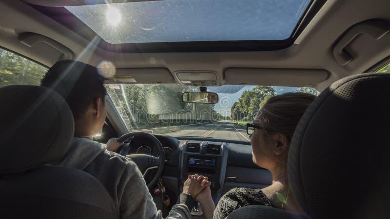 Πολυ-εθνική οδήγηση ζευγών σε ένα αυτοκίνητο, ένας άνδρας που κρατά το χέρι μιας γυναίκας στοκ εικόνες