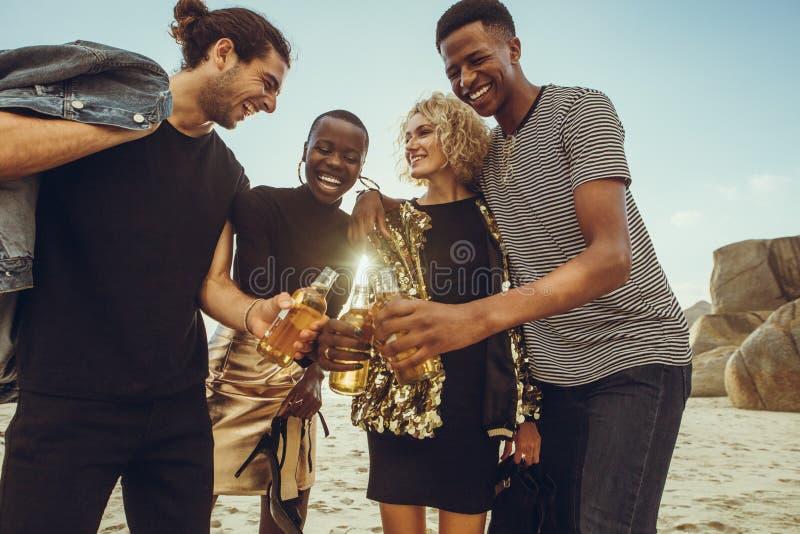 Πολυ-εθνική ομάδα φίλων που έχουν τις μπύρες στην παραλία στοκ εικόνα με δικαίωμα ελεύθερης χρήσης
