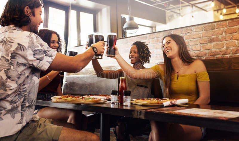 Πολυ-εθνική ομάδα φίλων που ψήνουν τα μη αλκοολούχα ποτά στον καφέ στοκ εικόνες