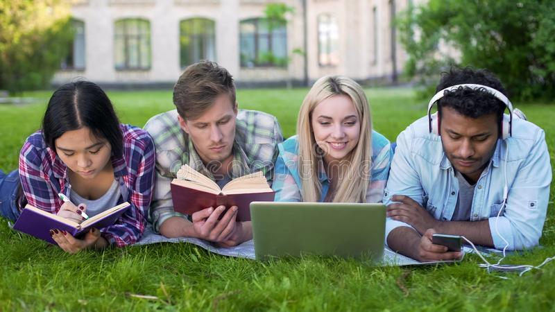 Πολυ-εθνικοί άνδρες και γυναίκες που κάνουν την εργασία στη χλόη στην πανεπιστημιούπολη, τριτοβάθμια εκπαίδευση στοκ φωτογραφίες