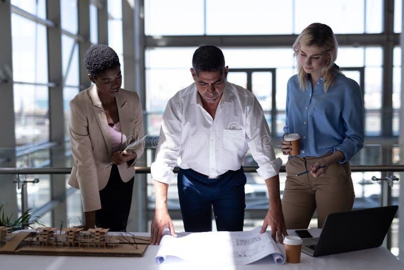 Πολυ-εθνικοί αρχιτέκτονες που εργάζονται στο γραφείο στην αρχή στοκ εικόνες