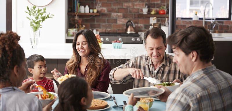 Πολυ οικογένεια παραγωγής που απολαμβάνει το γεύμα γύρω από τον πίνακα στο σπίτι από κοινού στοκ φωτογραφίες