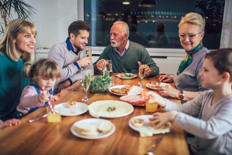 Πολυ οικογένεια παραγωγής που απολαμβάνει το γεύμα γύρω από τον πίνακα στοκ εικόνα