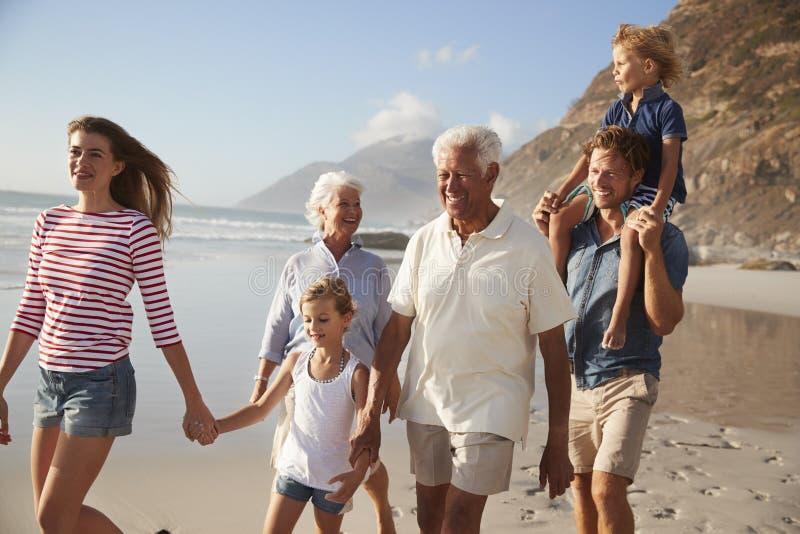 Πολυ οικογένεια παραγωγής στις διακοπές που περπατά κατά μήκος της παραλίας από κοινού στοκ εικόνα