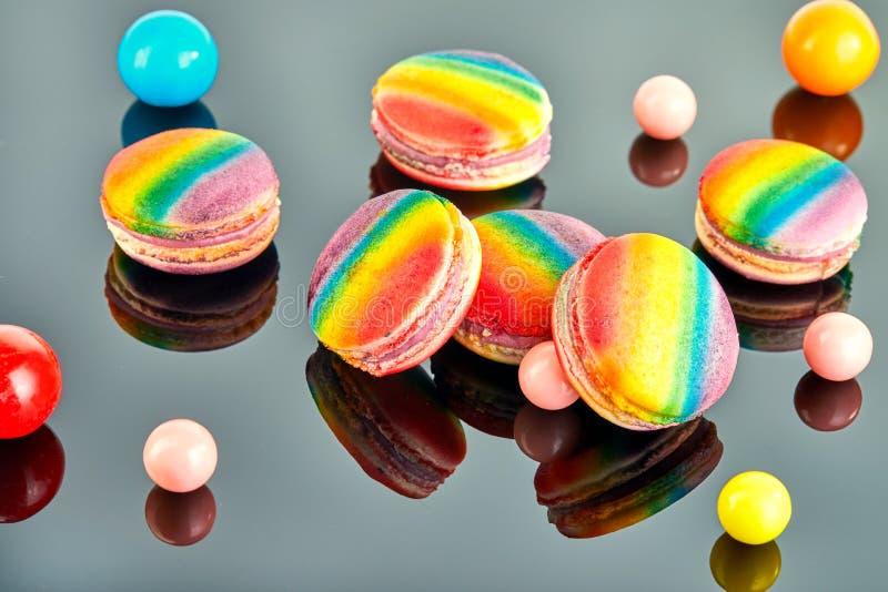 Πολυ που χρωματίζεται macaron και σφαίρες τσίχλας σε ένα γκρίζο υπόβαθρο με την αντανάκλαση στοκ φωτογραφίες