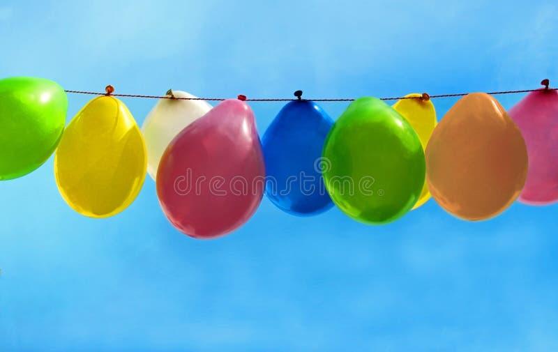 πολυ χρωματισμένα μπαλόνια που κρεμούν μπροστά από το μπλε ουρανό στοκ φωτογραφία