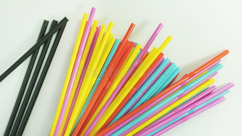 Πολυ χρωματισμένα πλαστικά άχυρα κατανάλωσης και μερικά μαύρα άχυρα κατανάλωσης εγγράφου που διαδίδονται σε μια ουδέτερη επιφάνει στοκ εικόνες