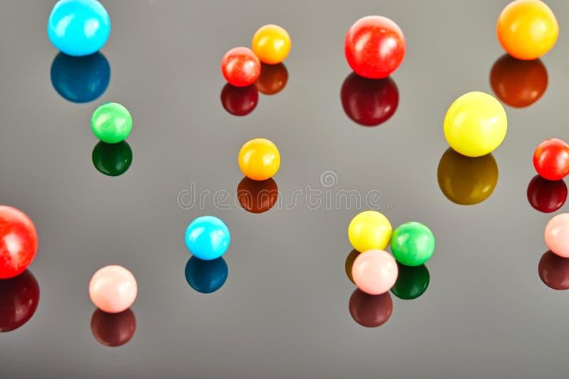 Πολυ χρωματισμένες σφαίρες της τσίχλας σε ένα γκρίζο υπόβαθρο με την αντανάκλαση στοκ φωτογραφίες