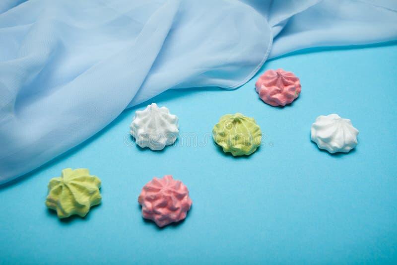 Πολυ χρωματισμένη γλυκιά παραδοσιακή μορφή μαρέγκας που απομονώνεται στο μπλε υπόβαθρο στοκ εικόνες