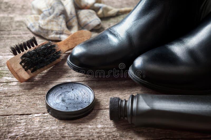 Πολωνική κρέμα, μαύρες μπότες, βούρτσα και στιλβωτής στοκ εικόνες