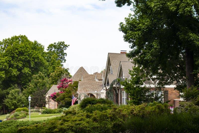 Πολύβλαστη φυλλώδης γειτονιά με τα όμορφα σπίτια και τον εξωραϊσμό και έναν κυματισμό αμερικανικών σημαιών στοκ εικόνα