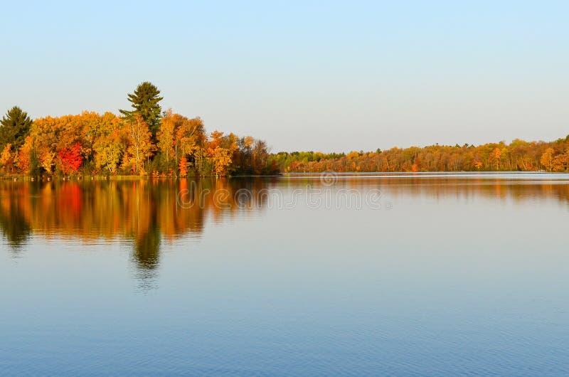 Πολύβλαστη χρωματισμένη πτώση αντανάκλαση δέντρων στο μπλε νερό λιμνών στοκ φωτογραφία με δικαίωμα ελεύθερης χρήσης