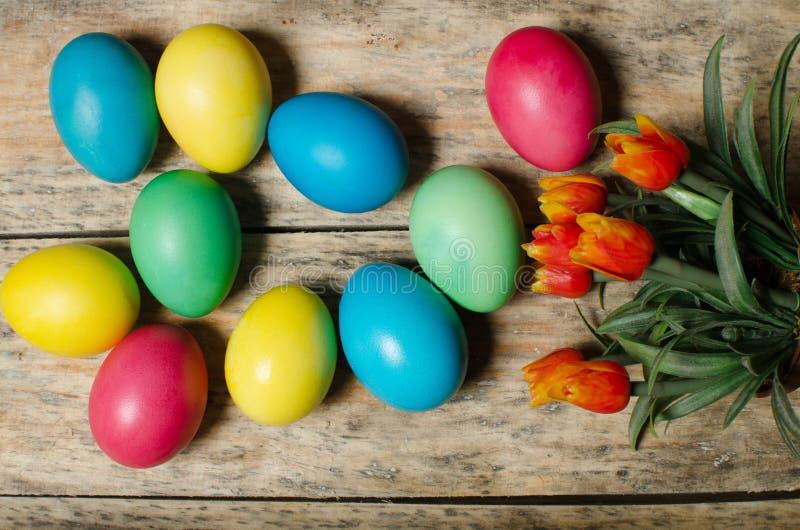 Πολύχρωμα αυγά Πάσχας σε ένα καλάθι σε ένα ξύλινο υπόβαθρο στοκ εικόνα