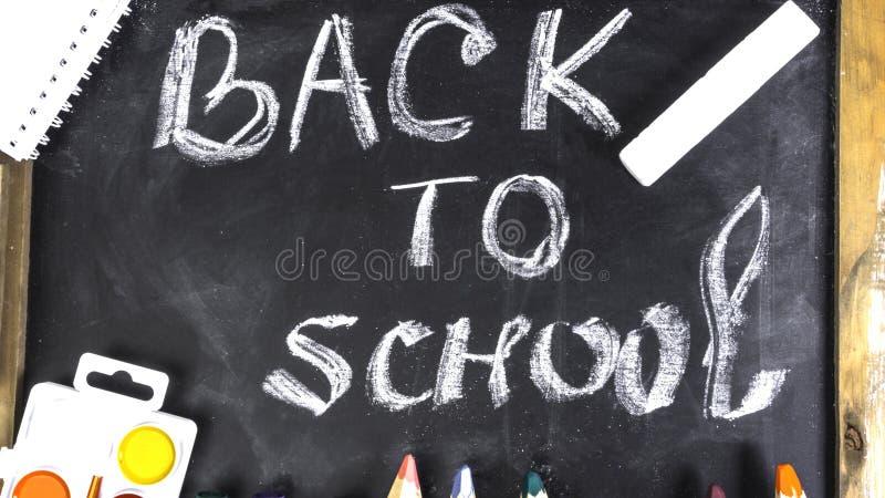 Πολύχρωμα σχολικά εφόδια σε μαύρο φόντο πίνακα Επίπεδη επικάλυψη στοκ εικόνες