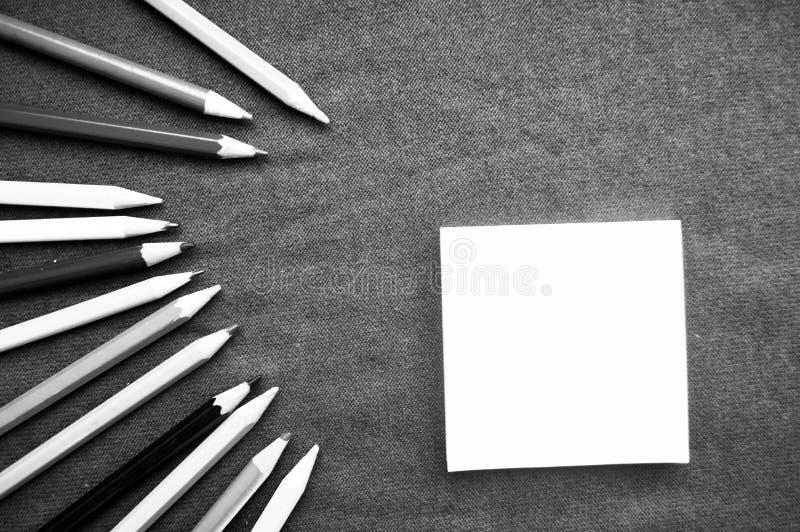 Πολύχρωμα, φωτεινά, ετερόκλητα μολύβια για το σχέδιο που βρίσκονται στο αριστερό σε μια σπείρα και ένα κομμάτι χαρτί στο δικαίωμα στοκ εικόνες με δικαίωμα ελεύθερης χρήσης