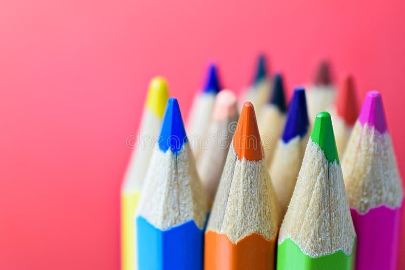 Πολύχρωμα pensils σε ένα κόκκινο υπόβαθρο - πίσω στο σχολείο concep στοκ εικόνα