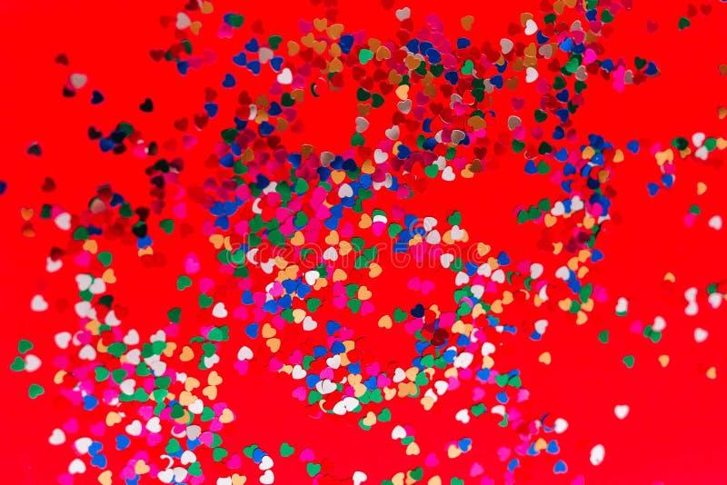 Πολύχρωμες καρδιές σε ένα κόκκινο υπόβαθρο Θέση για την επιγραφή στοκ φωτογραφία