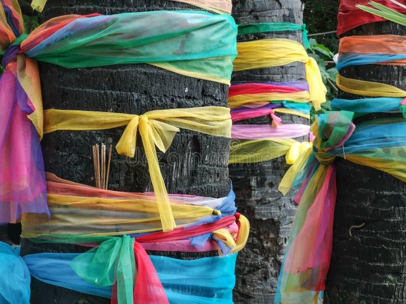 Πολύχρωμες κορδέλλες που τυλίγονται γύρω από τα ιερά και ιερά δέντρα κοντά στο βουδιστικό ναό στην Ταϊλάνδη στοκ φωτογραφία με δικαίωμα ελεύθερης χρήσης