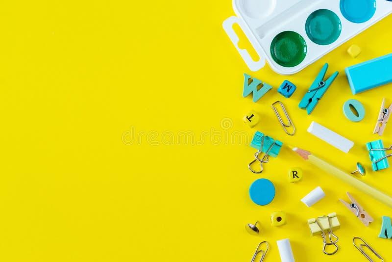 Πολύχρωμες σχολικές προμήθειες στο κίτρινο υπόβαθρο με το διάστημα αντιγράφων στοκ φωτογραφία