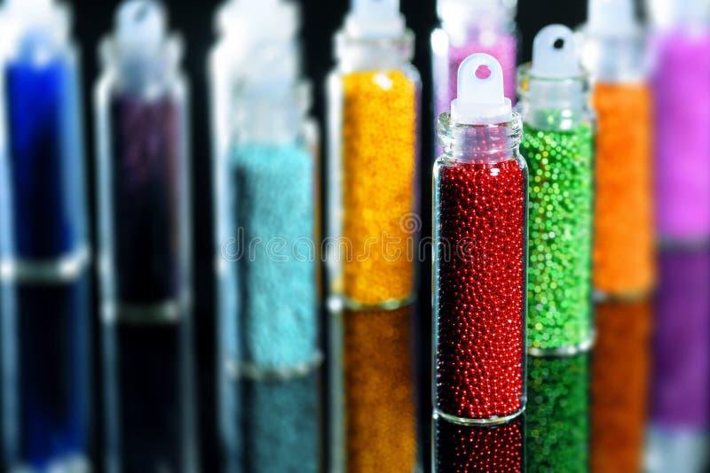Πολύχρωμες χάντρες στα μπουκάλια για το σχέδιο των καρφιών σε ένα μαύρο υπόβαθρο καθρεφτών στοκ εικόνες