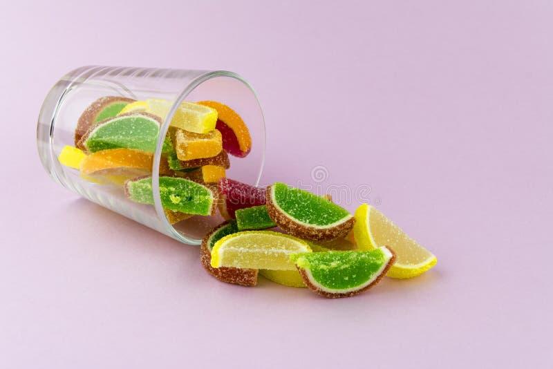 Πολύχρωμη μαρμελάδα υπό μορφή φετών εσπεριδοειδών σε ένα διαφανές γυαλί, το οποίο βρίσκεται σε ένα ρόδινο υπόβαθρο στοκ εικόνα