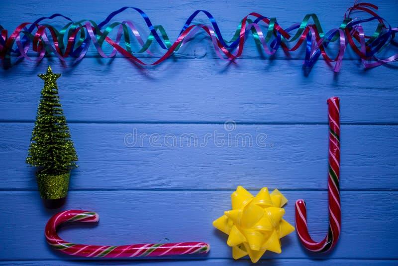 Πολύχρωμη ταινία στο μπλε ξύλινο υπόβαθρο με την κόκκινα καραμέλα και το χριστουγεννιάτικο δέντρο στοκ φωτογραφία με δικαίωμα ελεύθερης χρήσης