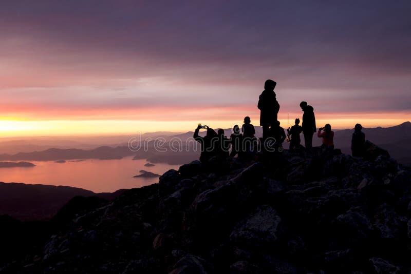 Πολύχρωμο ηλιοβασίλεμα Σκιαγραφίες των ανθρώπων πάνω από ένα βουνό που αγνοεί τη θάλασσα στοκ φωτογραφία με δικαίωμα ελεύθερης χρήσης