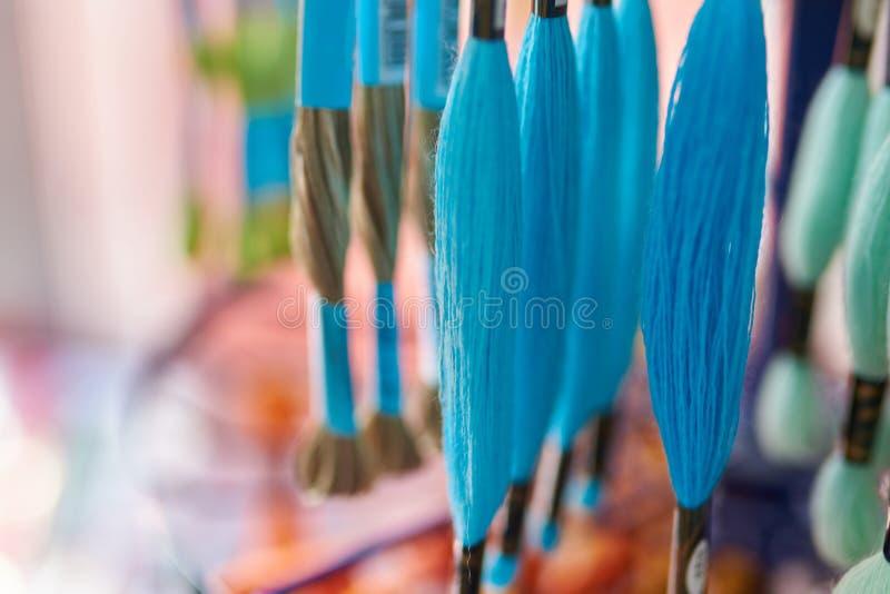 Πολύχρωμο νήμα νημάτων μαλλιού στα νηματοδέματα στη στάση στο κατάστημα, εκλεκτική εστίαση στοκ φωτογραφίες