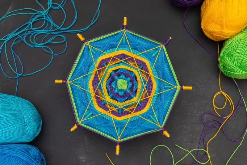 Πολύχρωμο χειροποίητο mandala στη μέση του σκοτεινού γκρίζου υποβάθρου και των χρωματισμένων yan νηματοδεμάτων γύρω από το στοκ φωτογραφίες