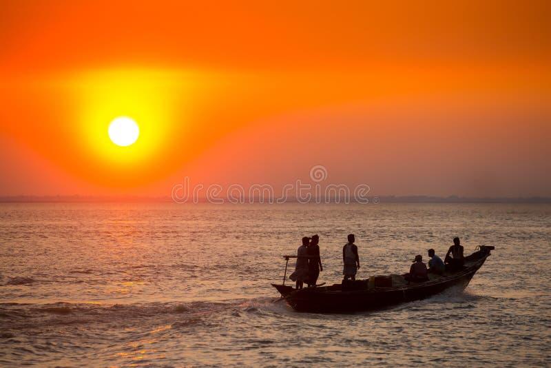 Πολύχρωμο χρυσό ηλιοβασίλεμα στη θάλασσα Οι ψαράδες επιστρέφουν σπίτι με ψάρια, χειροκίνητα στο ηλιοβασίλεμα στην παραλία Char Sa στοκ φωτογραφίες με δικαίωμα ελεύθερης χρήσης