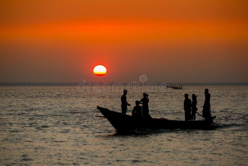 Πολύχρωμο χρυσό ηλιοβασίλεμα στη θάλασσα Οι ψαράδες επιστρέφουν σπίτι με ψάρια, χειροκίνητα στο ηλιοβασίλεμα στην παραλία Char Sa στοκ εικόνα