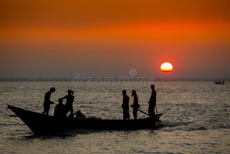 Πολύχρωμο χρυσό ηλιοβασίλεμα στη θάλασσα Οι ψαράδες επιστρέφουν σπίτι με ψάρια, χειροκίνητα στο ηλιοβασίλεμα στην παραλία Char Sa στοκ εικόνες