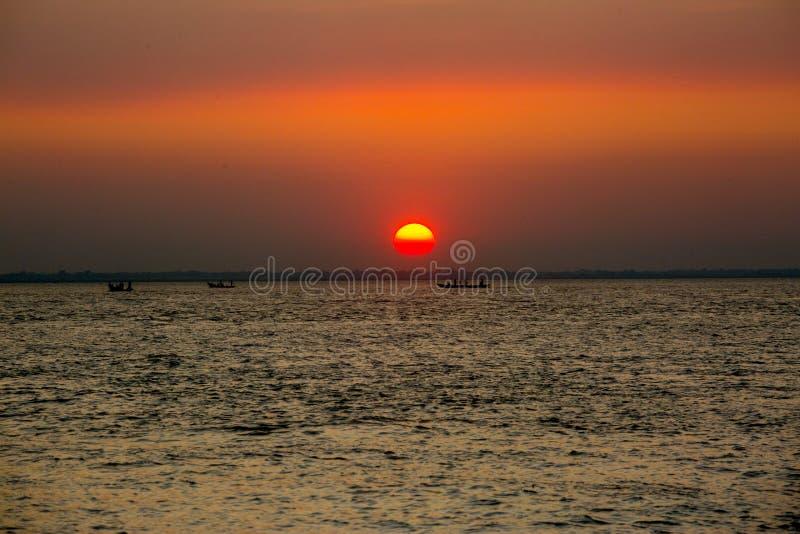 Πολύχρωμο χρυσό ηλιοβασίλεμα στη θάλασσα Οι ψαράδες επιστρέφουν σπίτι με ψάρια, χειροκίνητα στο ηλιοβασίλεμα στην παραλία Char Sa στοκ φωτογραφία