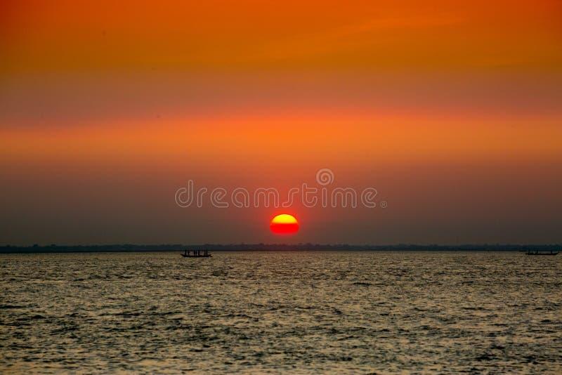 Πολύχρωμο χρυσό ηλιοβασίλεμα στη θάλασσα Οι ψαράδες επιστρέφουν σπίτι με ψάρια, χειροκίνητα στο ηλιοβασίλεμα στην παραλία Char Sa στοκ φωτογραφία με δικαίωμα ελεύθερης χρήσης