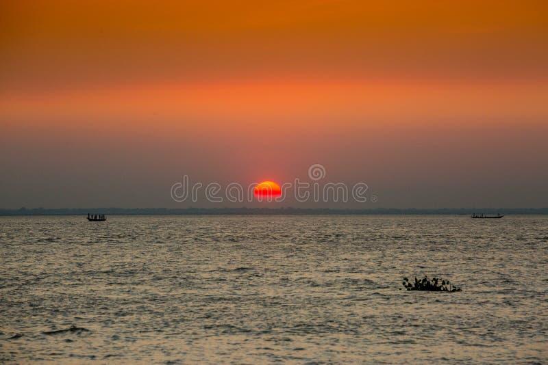 Πολύχρωμο χρυσό ηλιοβασίλεμα στη θάλασσα Οι ψαράδες επιστρέφουν σπίτι με ψάρια, χειροκίνητα στο ηλιοβασίλεμα στην παραλία Char Sa στοκ φωτογραφίες
